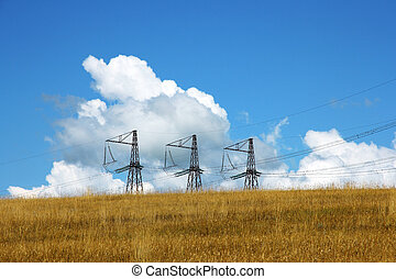 Three electrical towers  background of clouds and sky