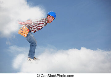 Photomontage of a young workman walking on the clouds