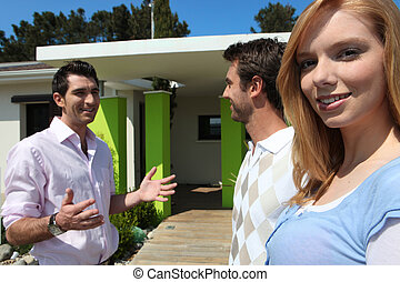Twentysomething friends outside a modern house