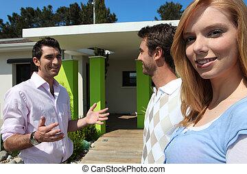 Twentysomething friends outside a modern house
