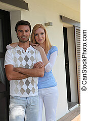 Young couple standing in front of their house