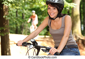 Smiling young woman riding her bike through the forest