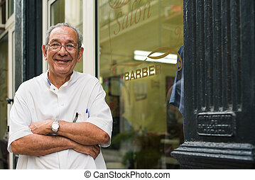 portrait of old barber smiling in hair salon - senior...