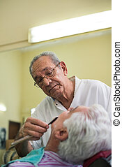 Elderly barber with razor shaving client in barber shop -...