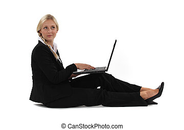 A businesswoman sitting on the floor with her laptop