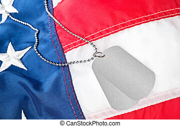 Dog tags on American flag - A pair of blank dog tags on an...