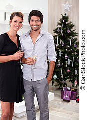 Couple drinking champagne by the Christmas tree