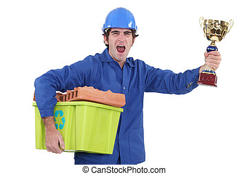 A construction worker holding a trophy and a recycling basket.