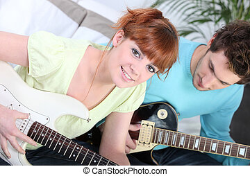 Couple sat playing the electric guitar