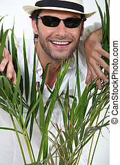 Portrait of a man between the branches of a plant