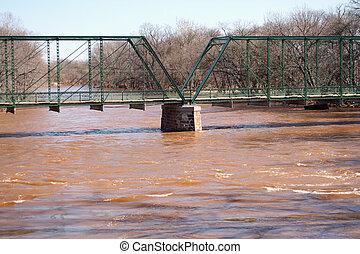 Old metal Bridge over rising flood waters - A Old metal...