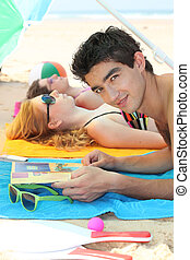 Couple on the beach with magazine