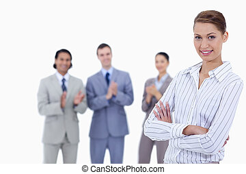 Close-up of a woman crossing her arms with business people applauding while watching her against white background