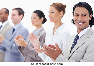 Close-up of a business team smiling and applauding while...