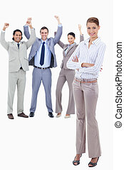 Secretary smiling and crossing her arms with very enthusiastic business people behind her against white background