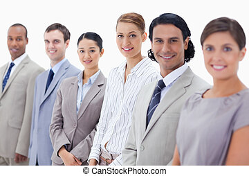 Close-up of smiling business people looking straight with...