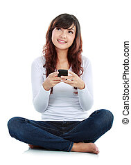Woman text messaging - Woman sitting on floor and text...