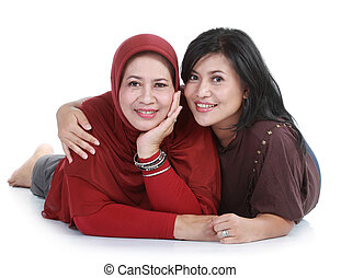 muslim woman with her daughter lying on isolated over white...