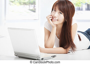 asian young woman lying on floor doing homework on laptop