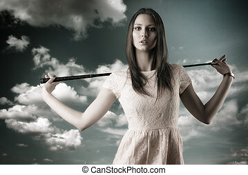 beautiful woman with golfclub, she looks in to the lens