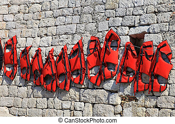 Float vests - Red floating safety vests drying at sunny day