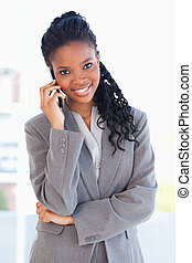 Smiling employee standing upright seriously and talking on a...
