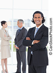 Young smiling executive standing upright in front of two...