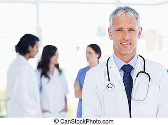 Mature and calm doctor standing upright in front of his...