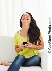 Happy Latino looking up while holding her cellphone