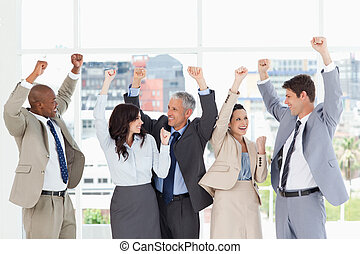 Smiling business people looking at each other and raising their arms in success