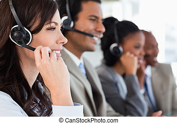 Young employee working with a headset and accompanied by her...