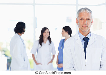 Serous doctor standing in the foreground and accompanied by...