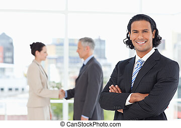 Young smiling executive standing upright in a suit with...