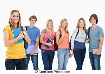 A smiling group of college students standing as one girl...