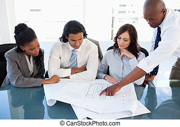 Young executive explaining an idea to his colleagues using...