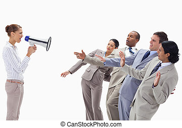 Woman yelling at co-workers through a megaphone against...