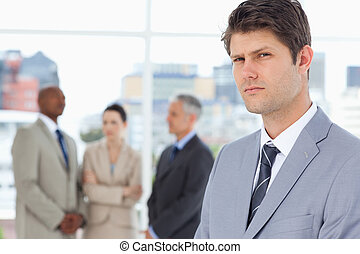 Young businessman with a stern look standing in front of executives