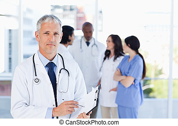 Mature doctor pointing at something on his clipboard -...