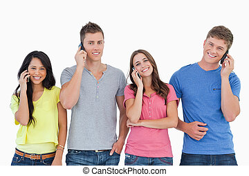 A group of friends of smiling as they all make calls and look into the camera