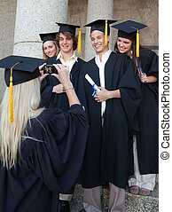 Blonde graduate taking a picture of her friend