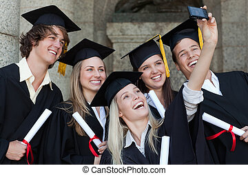 Close-up of happy graduates taking a picture of themselves...