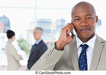 Young serious executive in a suit talking on the phone while...