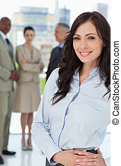 Young executive woman standing upright with her hands...