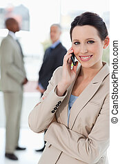 Young businesswoman talking on the mobile phone with her arms crossed
