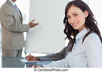 Smiling businesswoman writing in a notebook during a...