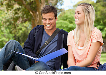 Smiling tutor helping a teenager to revise