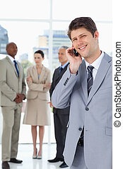 Smiling businessman using a mobile phone in front of his team