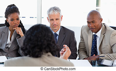 A business team is earnestly listening to an associate -...