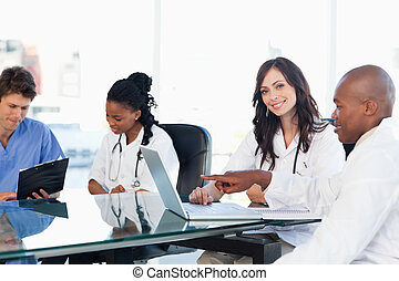 Two smiling medical interns working at the computer near...