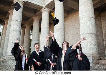 Graduates throwing their hats in the sky in front of their...